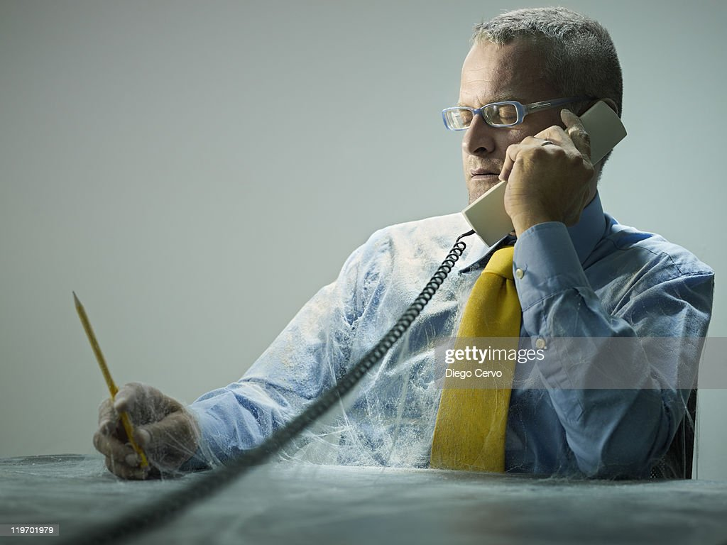 Caucasian businessman covered in cobwebs talking on telephone : Stock Photo