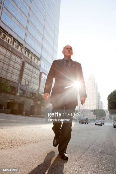 Caucasian businessman crossing urban street