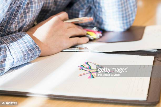 Caucasian businessman doodling in office