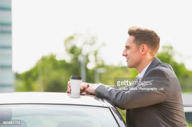 Caucasian businessman drinking cup of coffee near car