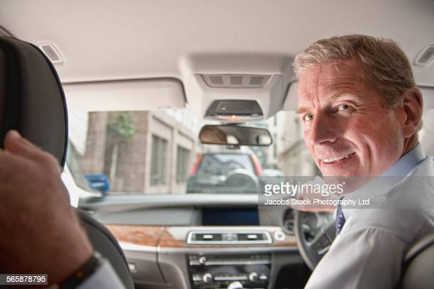 Caucasian businessman driving car in reverse