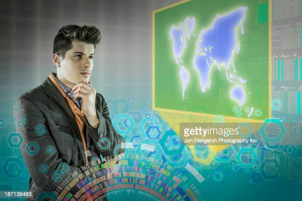Caucasian businessman examining illuminated holograms