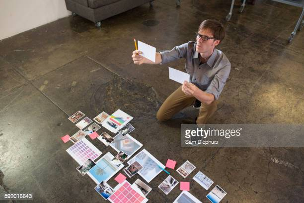 Caucasian businessman examining paperwork on office floor
