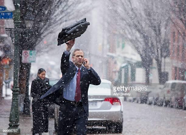 Caucasian businessman hailing taxi in snow
