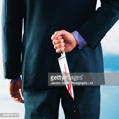 Caucasian businessman hiding bloody dagger behind back