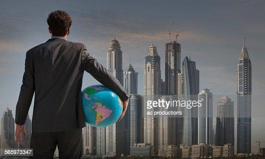 Caucasian businessman holding globe near Qatar cityscape, Qatar