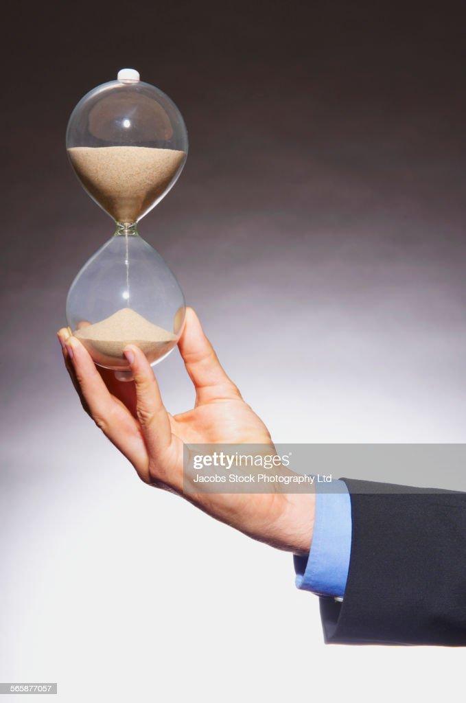 Caucasian businessman holding hourglass : Stock Photo
