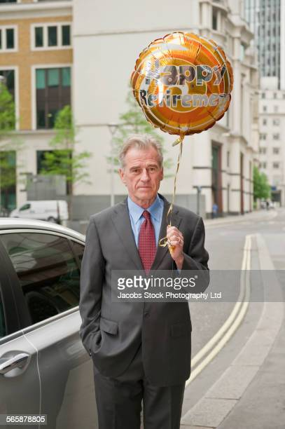 Caucasian businessman holding retirement balloon on city sidewalk