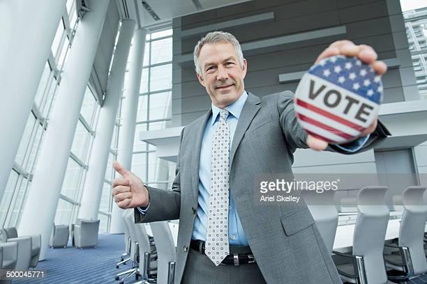 Caucasian businessman holding Vote' button