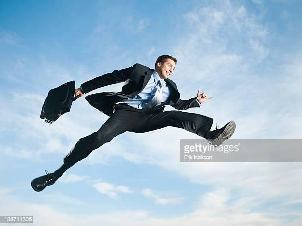Caucasian businessman jumping in air