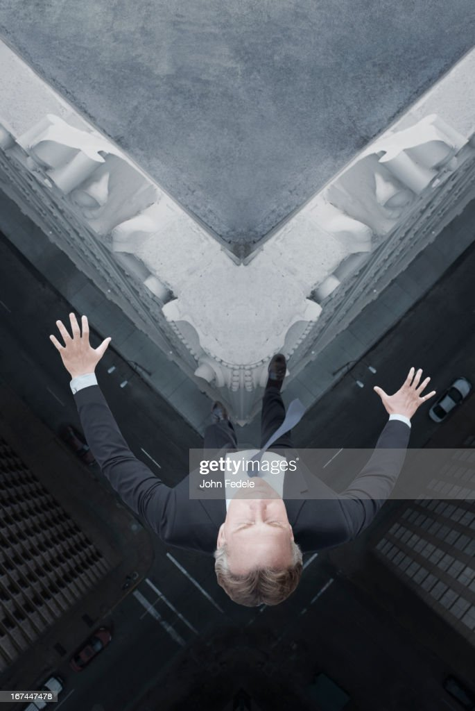 Caucasian businessman jumping off skyscraper : Stock Photo