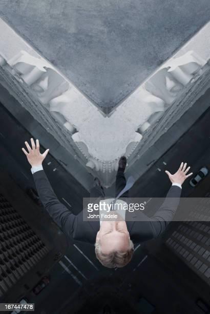 Caucasian businessman jumping off skyscraper