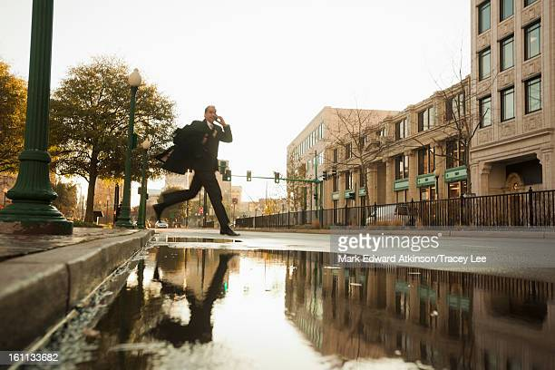 Caucasian businessman jumping over urban puddle