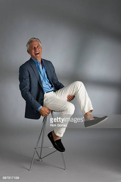 Caucasian businessman laughing on stool