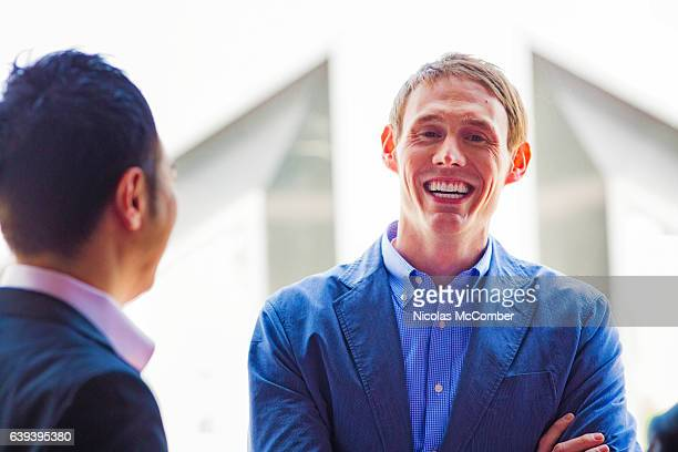 Caucasian businessman laughs while bonding with Japanese colleague