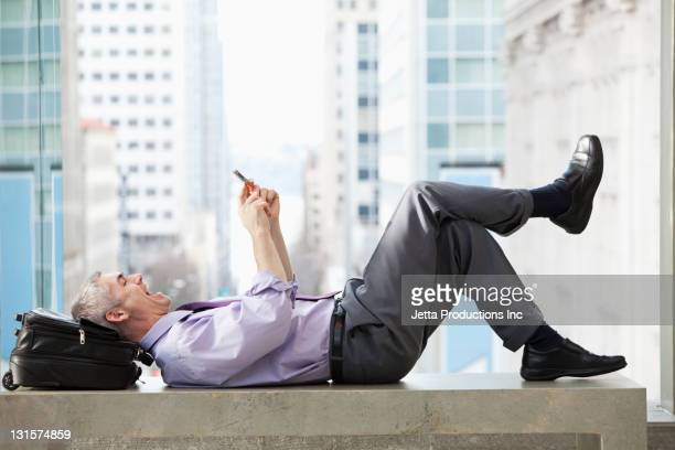 Caucasian businessman laying on bench text messaging