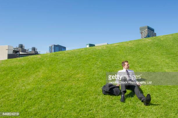 Caucasian businessman laying on grassy hillside