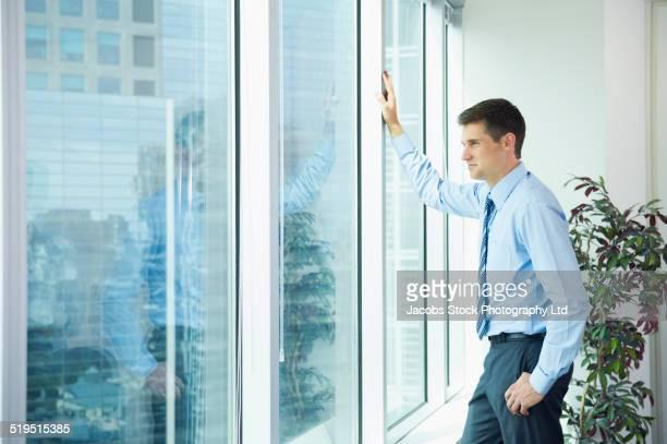 Caucasian businessman leaning on office window