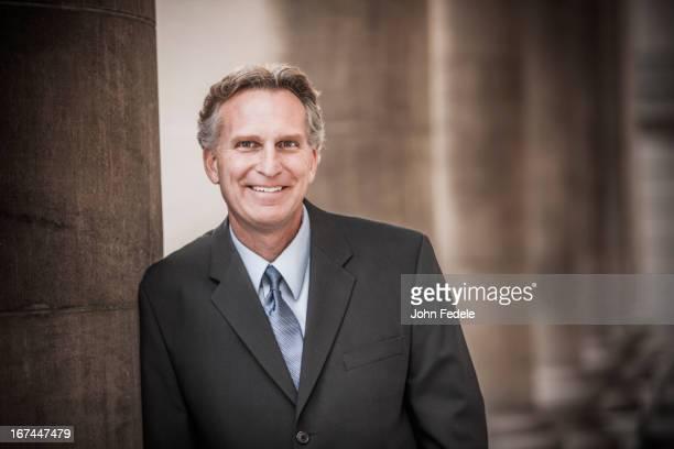 Caucasian businessman leaning on pillar
