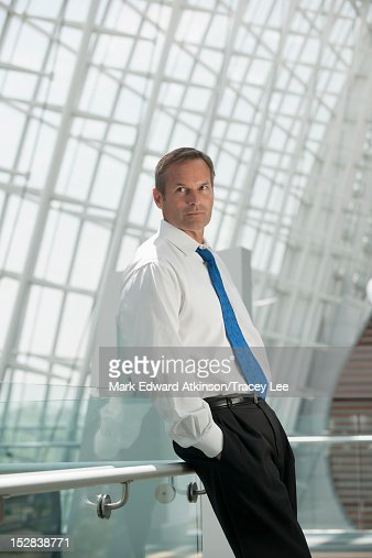 Caucasian businessman leaning on railing with hands in pockets : Stock Photo
