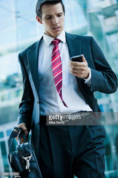 Caucasian businessman looking at cell phone outdoors