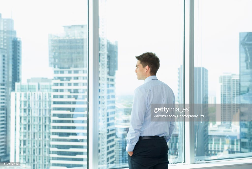 Caucasian businessman looking at cityscape from office window