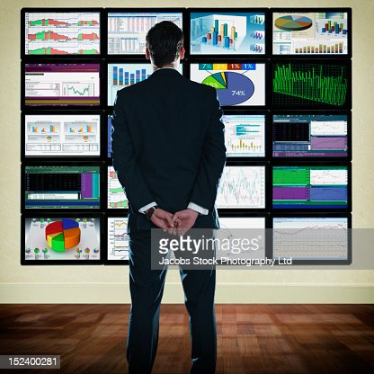 Caucasian businessman looking at graphs on monitors : Stock Photo