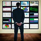 Caucasian businessman looking at graphs on monitors