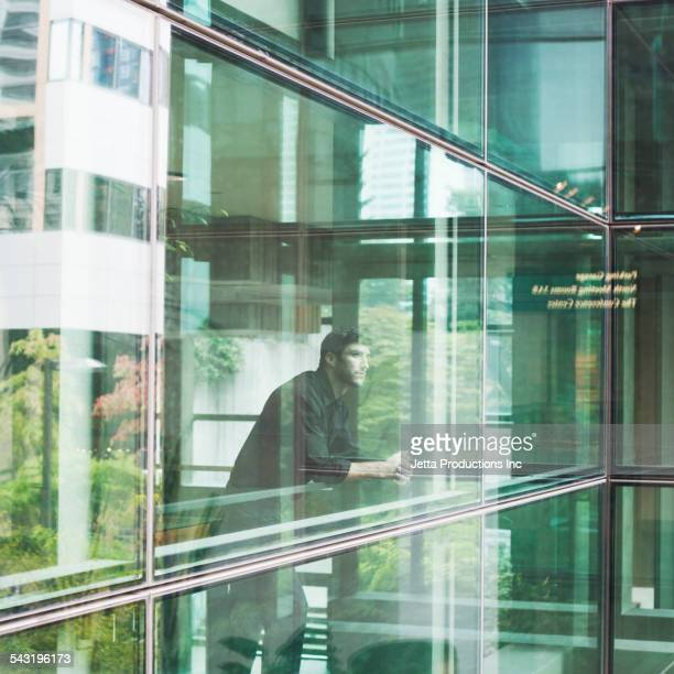 Caucasian businessman looking out glass window