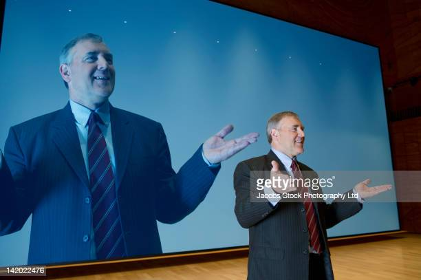 Caucasian businessman making speech in front of monitor