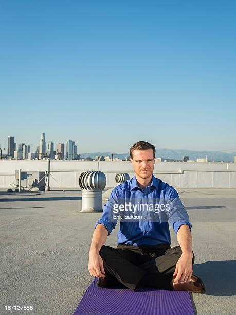 Caucasian businessman meditating on urban rooftop