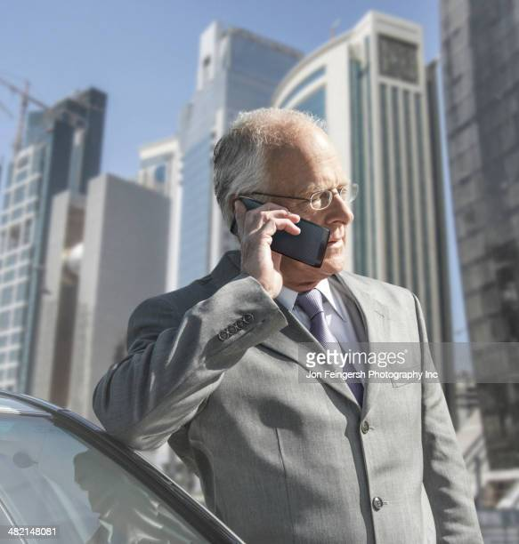 Caucasian businessman on cell phone by city skyline
