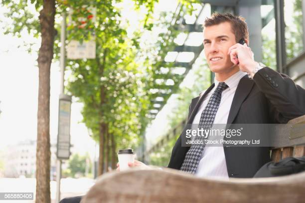 Caucasian businessman on cell phone waiting for bus