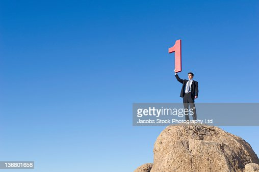 Caucasian businessman on rock lifting large number 1 : Stock Photo