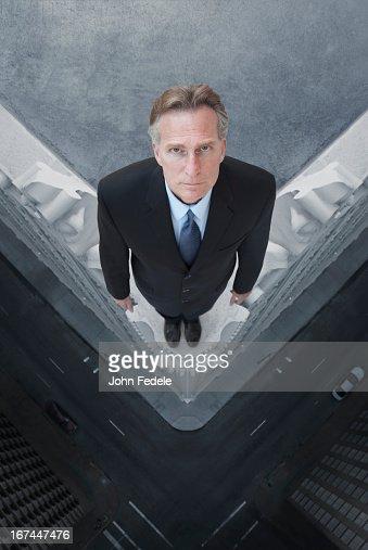 Caucasian businessman on skyscraper ledge