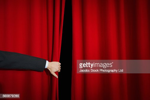 Caucasian businessman opening stage curtain