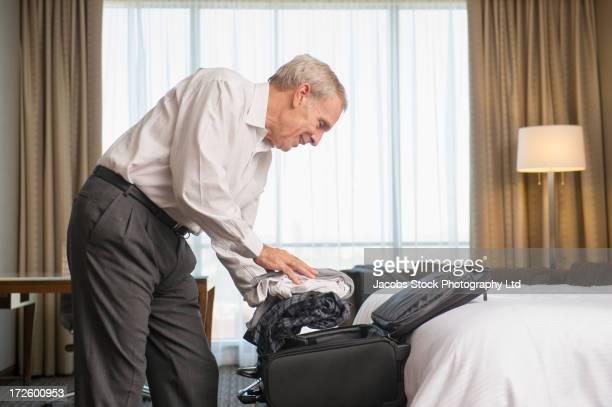 Caucasian businessman packing suitcase in hotel room
