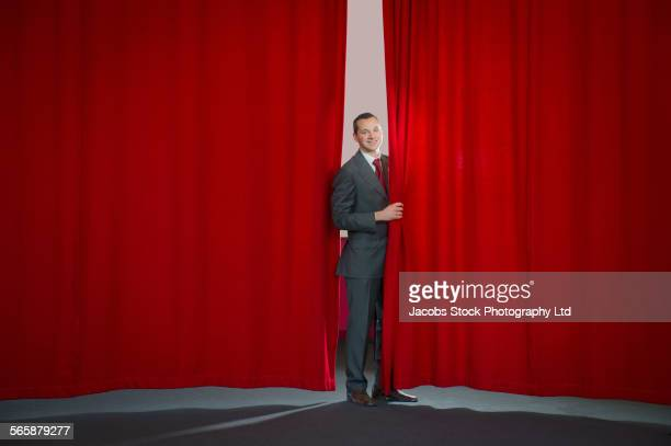 Caucasian businessman peering around curtain on stage