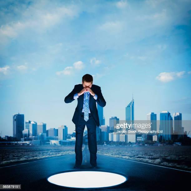 Caucasian businessman peering into glowing hole in street, Melbourne, Victoria, Australia