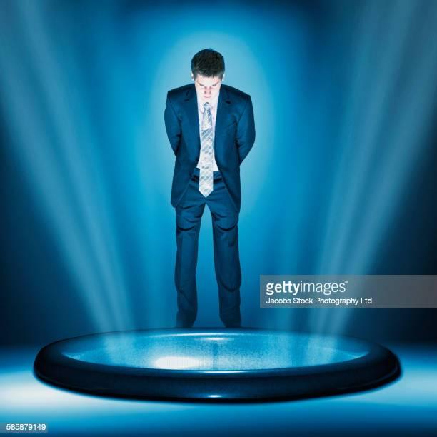 Caucasian businessman peering into glowing hole