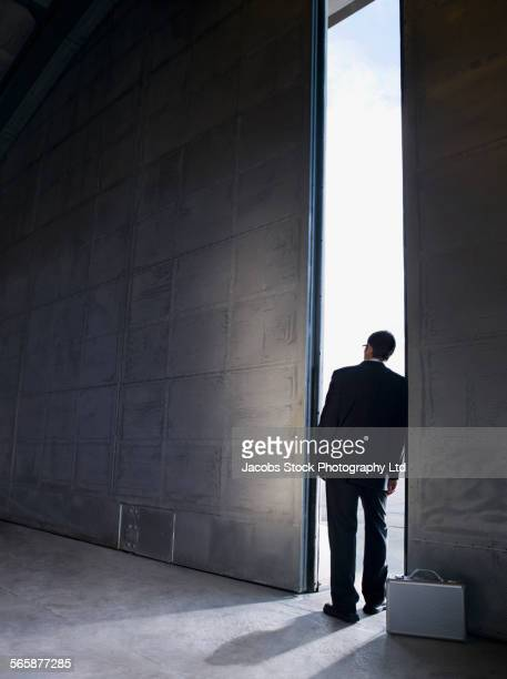 Caucasian businessman peering out warehouse doors
