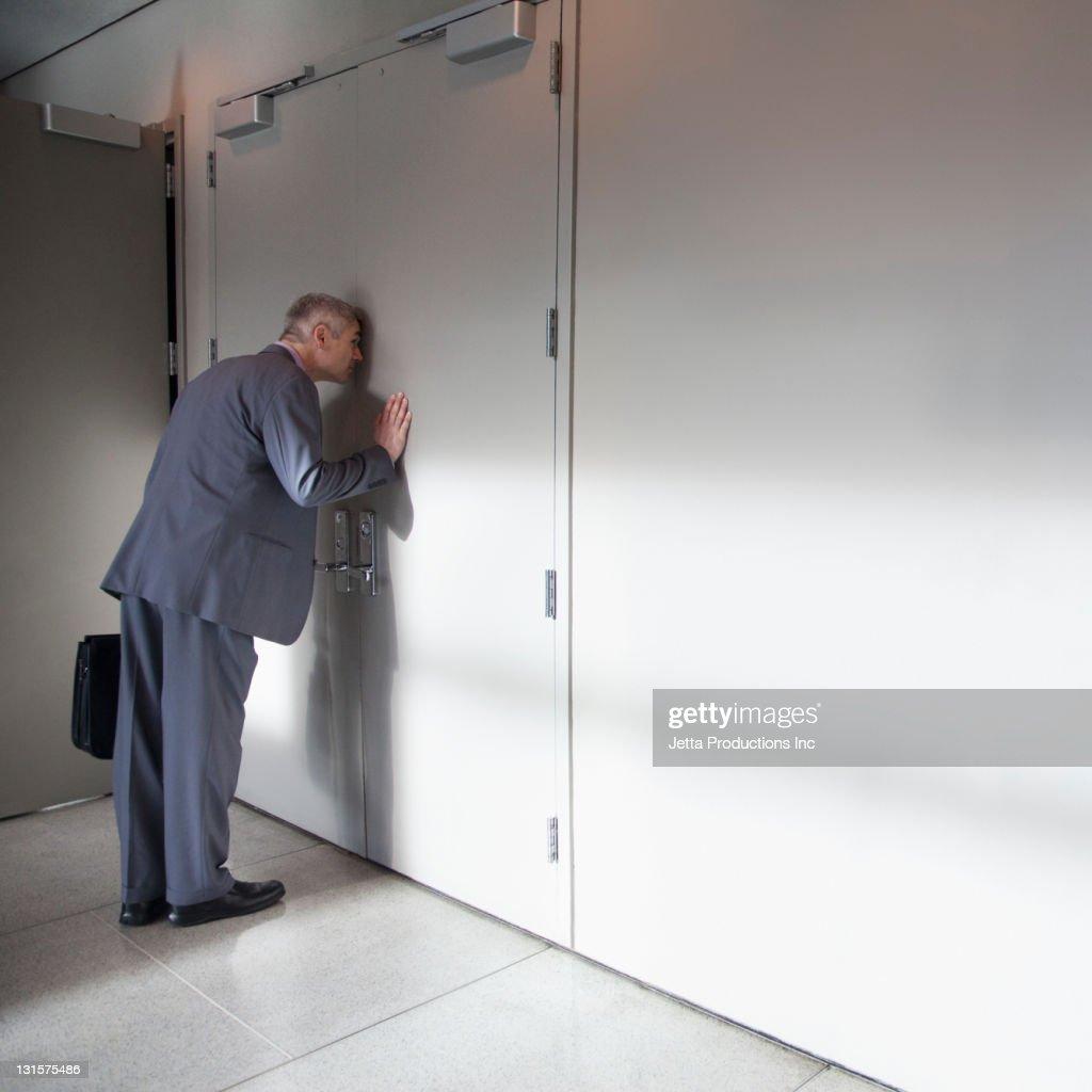 Caucasian businessman peering through office door : Stock Photo