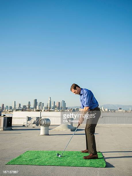 Caucasian businessman playing golf on urban rooftop
