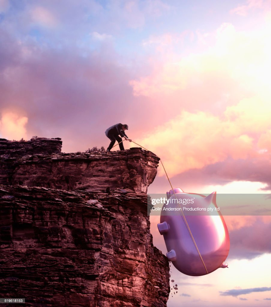 Caucasian businessman pulling large piggy bank up cliff