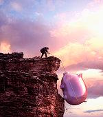 Caucasian businessman pulling large piggy bank up cliff