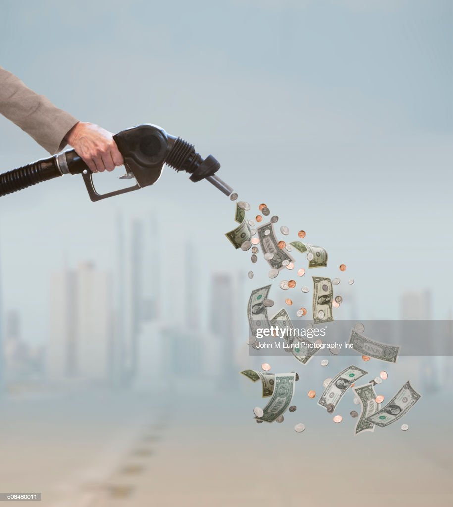 Caucasian businessman pumping expensive fuel : Stock Photo