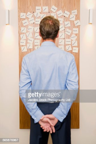 Caucasian businessman reading adhesive notes on office wall