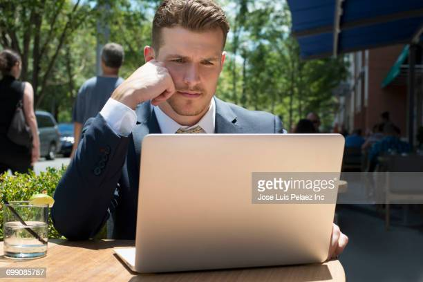 Caucasian businessman reading laptop at cafe outdoors
