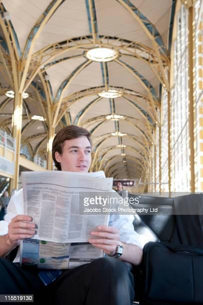 Caucasian businessman reading newspaper in airport