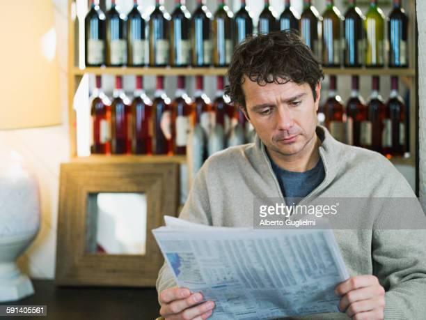 Caucasian businessman reading newspaper in cafe
